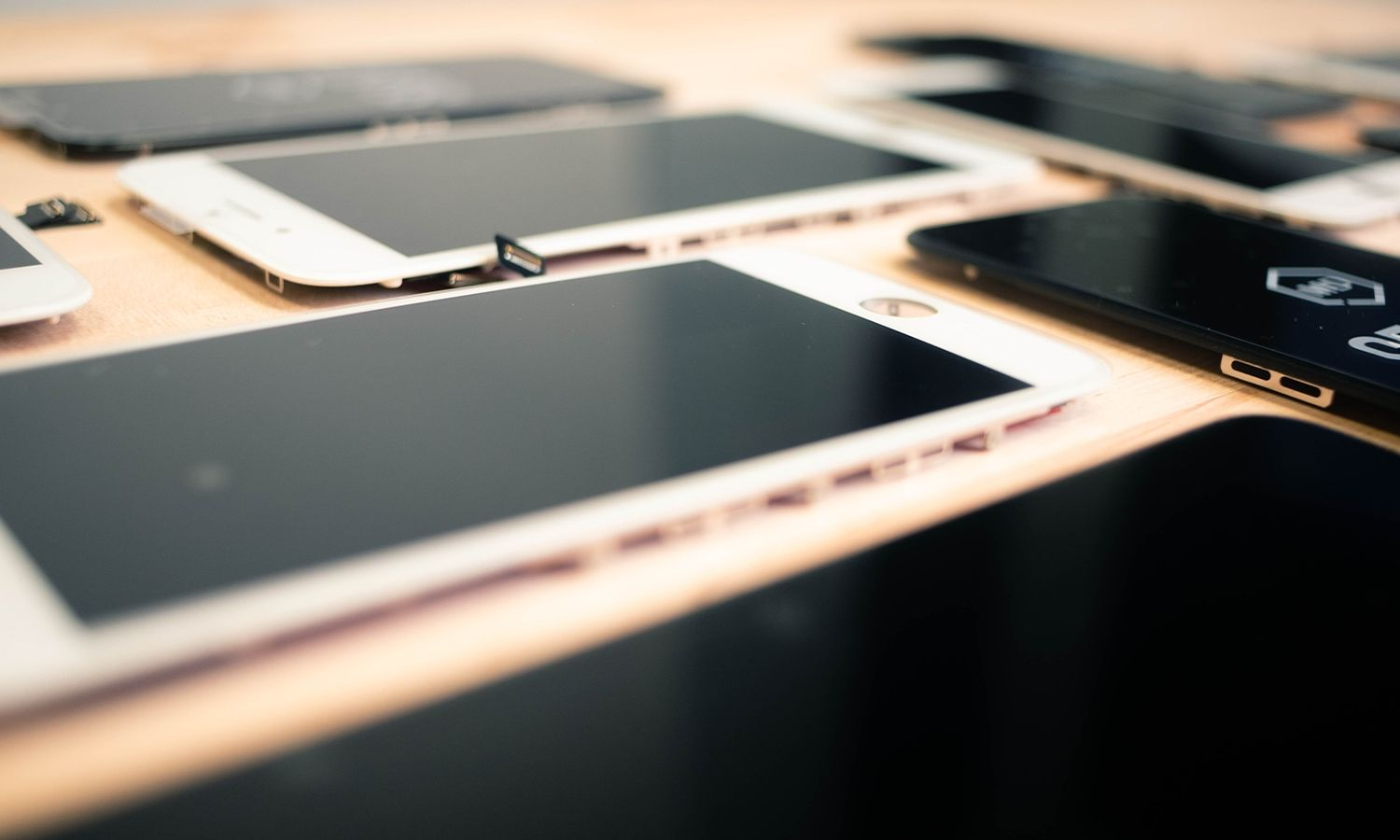 Replacement screens for iPhones arranged on a table. High-quality replacement parts available at Mobile Defenders.